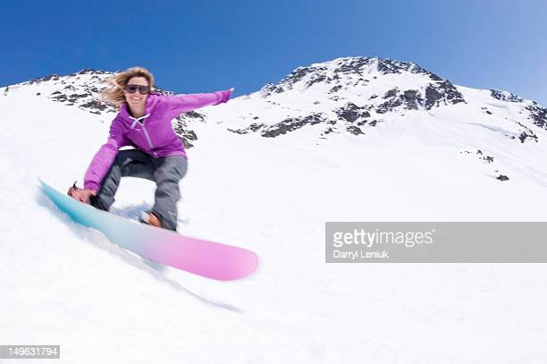 Young female snowboarder carving down snowy slope.