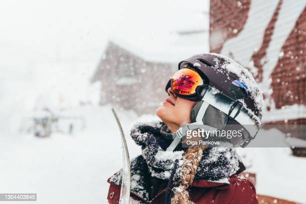 a young female snowboarder dressed in snowboard gear enjoys a heavy snowfall after snowboarding. protective helmet and ski goggles. - événement sportif d'hiver photos et images de collection