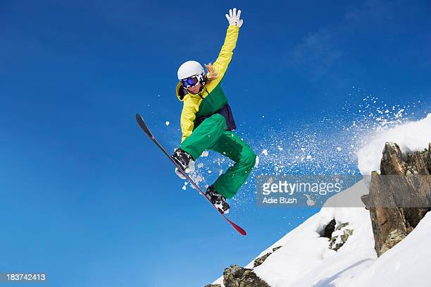 young female snowboarder jumping - boarding stock pictures, royalty-free photos & images