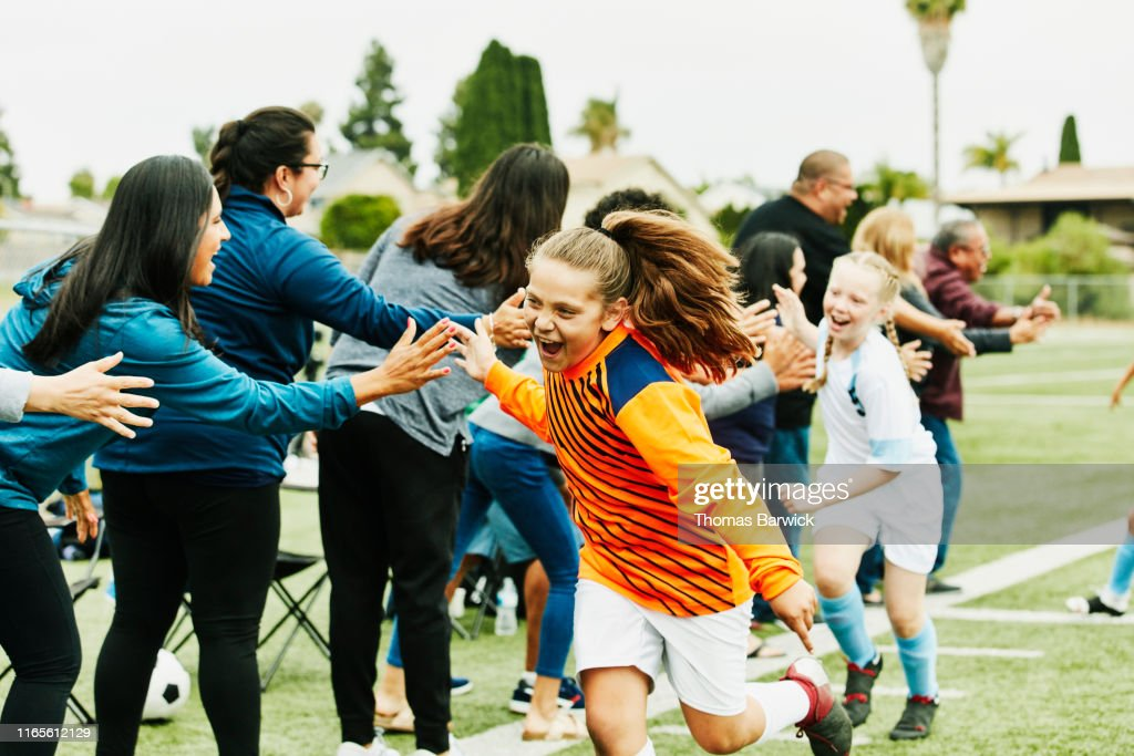 Young female soccer goalie high fiving parents on sidelines after soccer game : Stock Photo