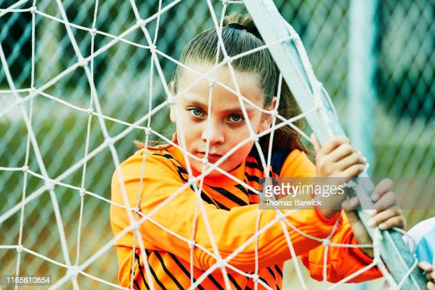 Young female soccer goalie moving goal into place before practice