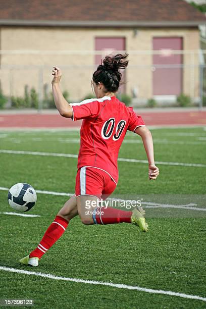 Junge weibliche Fußball-Spieler in Rot Verfolgungsjagden-Hüpfen Ball