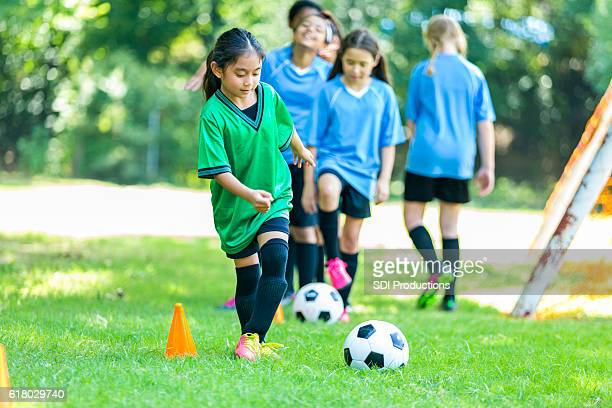 Young female soccer player practices drills