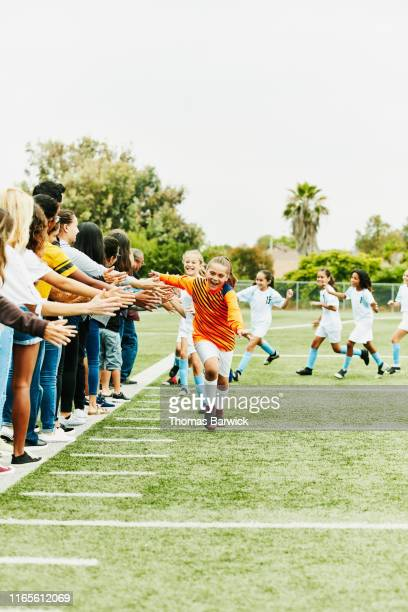 young female soccer player running though line of high fives with families on sidelines after game - hingabe stock-fotos und bilder