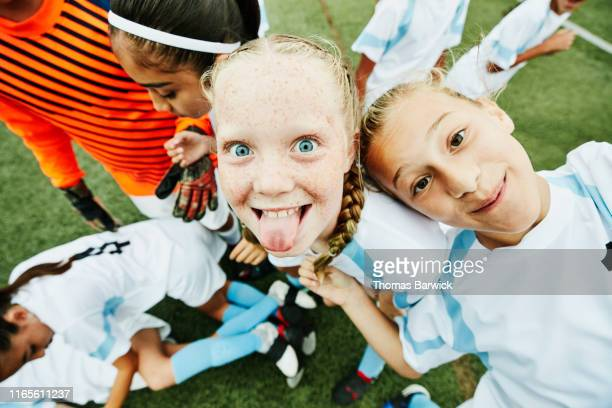 young female soccer player sticking out tongue and playing with teammates after game - naughty america member stock pictures, royalty-free photos & images