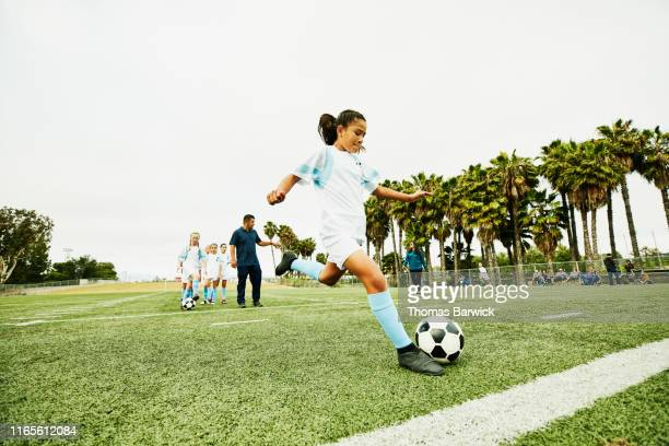 young female soccer player taking warm up shot before game - kicking stock pictures, royalty-free photos & images