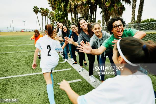young female soccer players high fiving parents on sidelines after soccer game - sport stock pictures, royalty-free photos & images