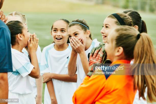 young female soccer players laughing together - camiseta deportiva fotografías e imágenes de stock