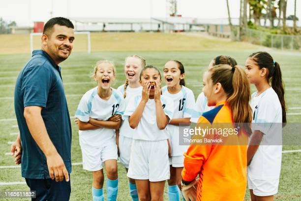 young female soccer players laughing with coach during practice - equipo de fútbol fotografías e imágenes de stock