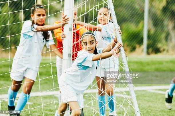 Young female soccer players moving goal together before practice