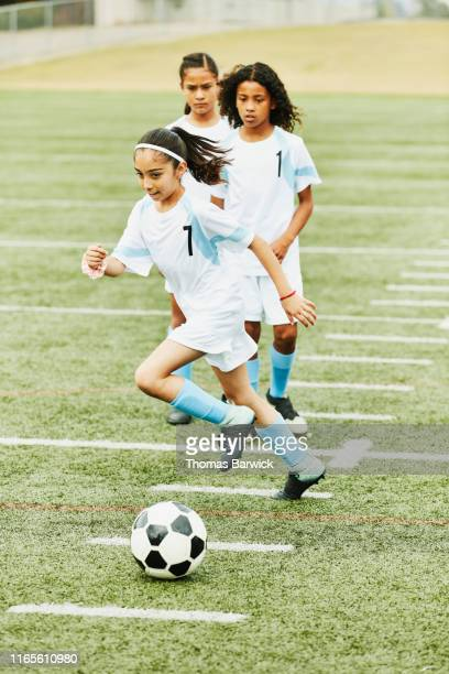 Young female soccer players running warm up drills on field before game