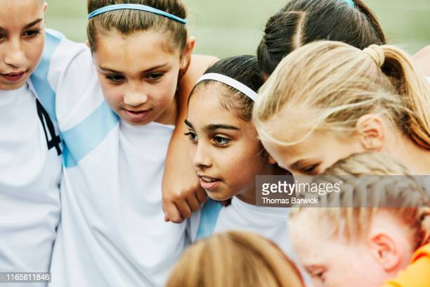 Young female soccer players with arms around each other huddled together before game