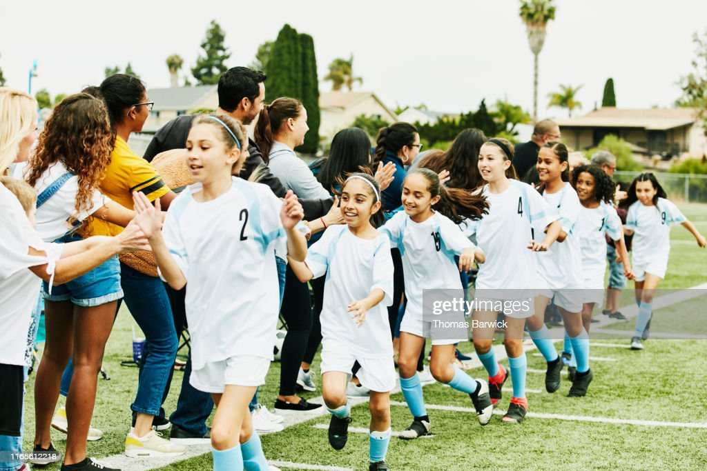 Young female soccer team giving high fives to parents on sidelines after game : Stock Photo