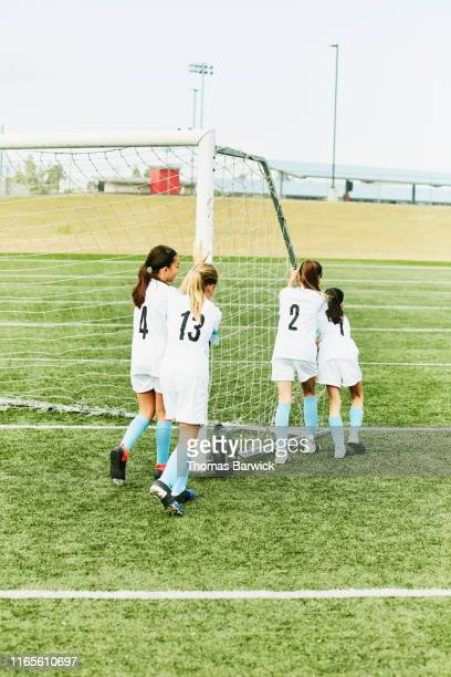 young female soccer team moving goal into place on field before practice - seulement des enfants photos et images de collection