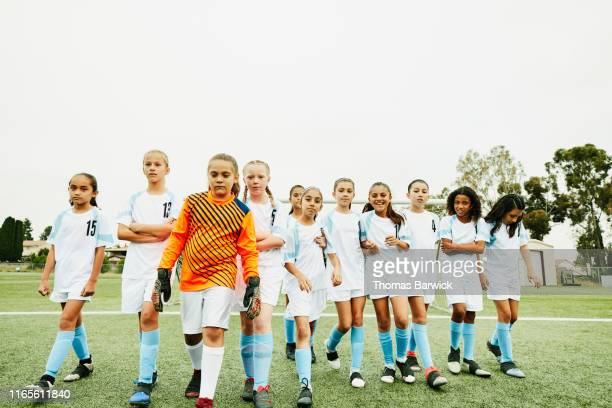 Young female soccer team walking onto field before game