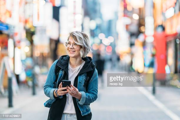 young female solo traveler using smart phone in city - israeli ethnicity stock pictures, royalty-free photos & images