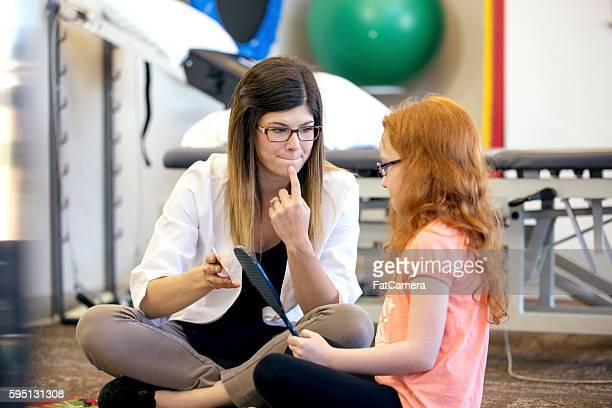 Young female speech therapist helping a young patient