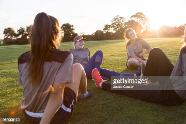 young female sports players sit on sports field talking and laughing in the evening light