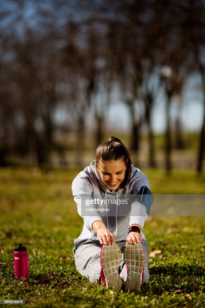Young female sretching in the park : Stock Photo