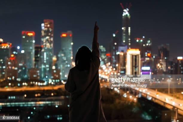 young female standing in front of modern city - gelegenheit stock-fotos und bilder