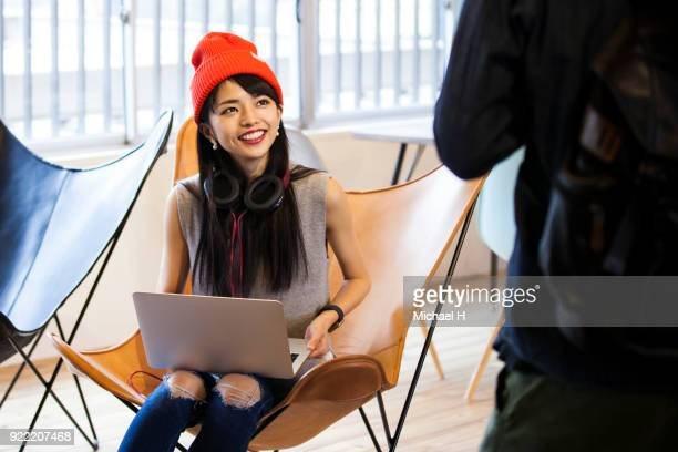 Young female start up business woman talking with colleague in office
