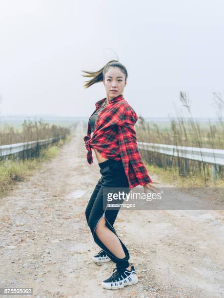 young female street dancer daning at country road