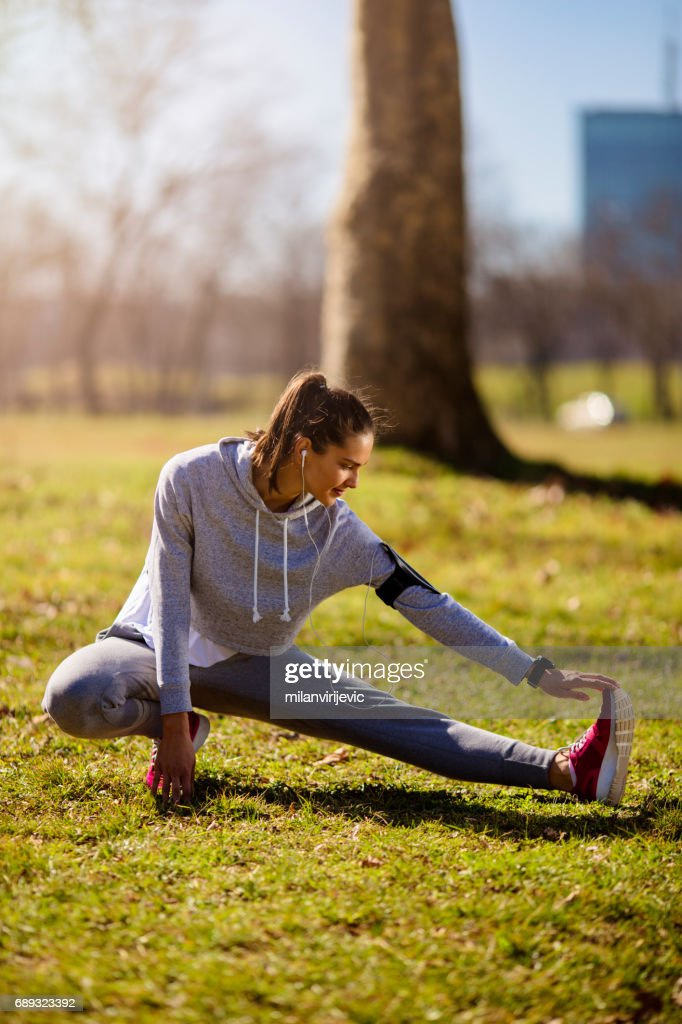 Young female stretching in city park : Stock Photo