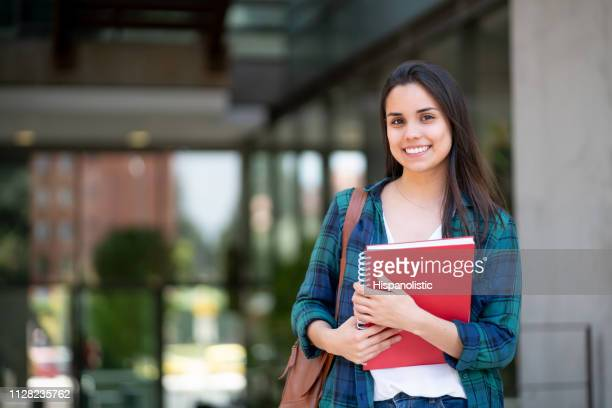 young female student at university campus holding her notebooks while smiling at camera - academy stock pictures, royalty-free photos & images