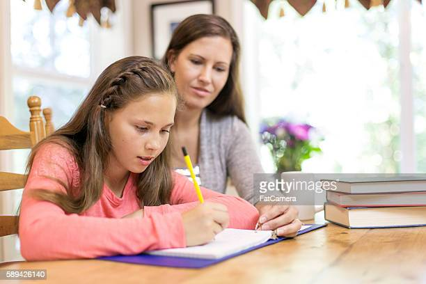 Young female student gets help on homework from mom