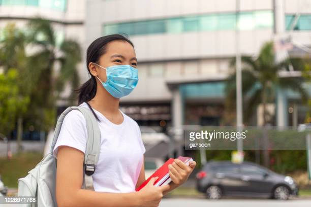 young female student going to school wearing protective facemask - east asian ethnicity stock pictures, royalty-free photos & images