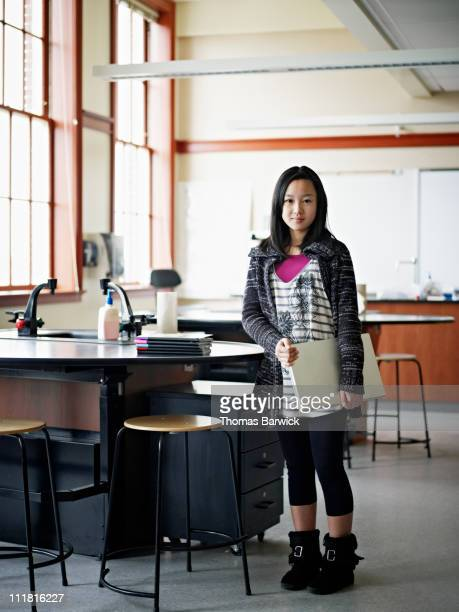 Young female student holding laptop in classroom