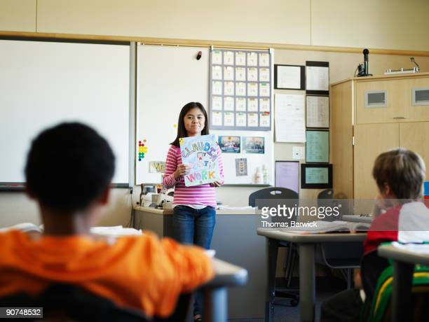 young female student presenting work in classroom - apresentação discurso imagens e fotografias de stock