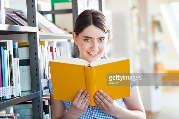 Young female student reading a book at the library