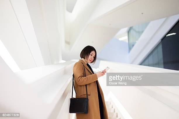 young female student reading text message in campus - leather purse stock pictures, royalty-free photos & images