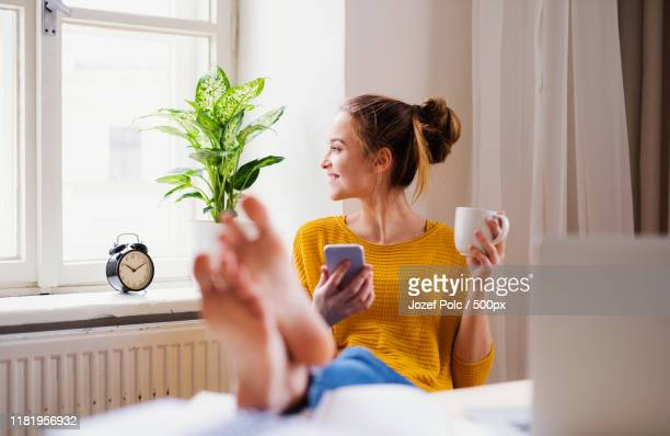 a young female student sitting at the table, using smartphone when studying - teenage girls feet stock-fotos und bilder