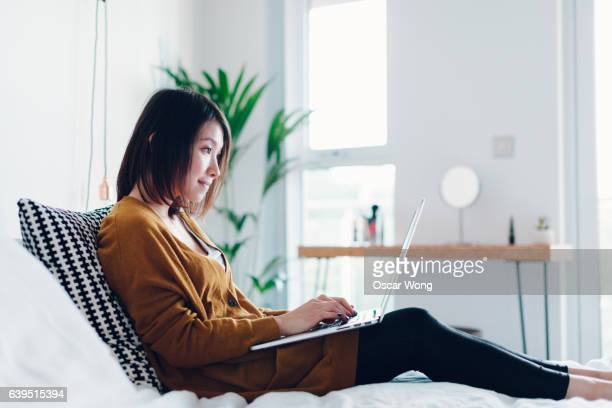 Young female student studying on laptop at home