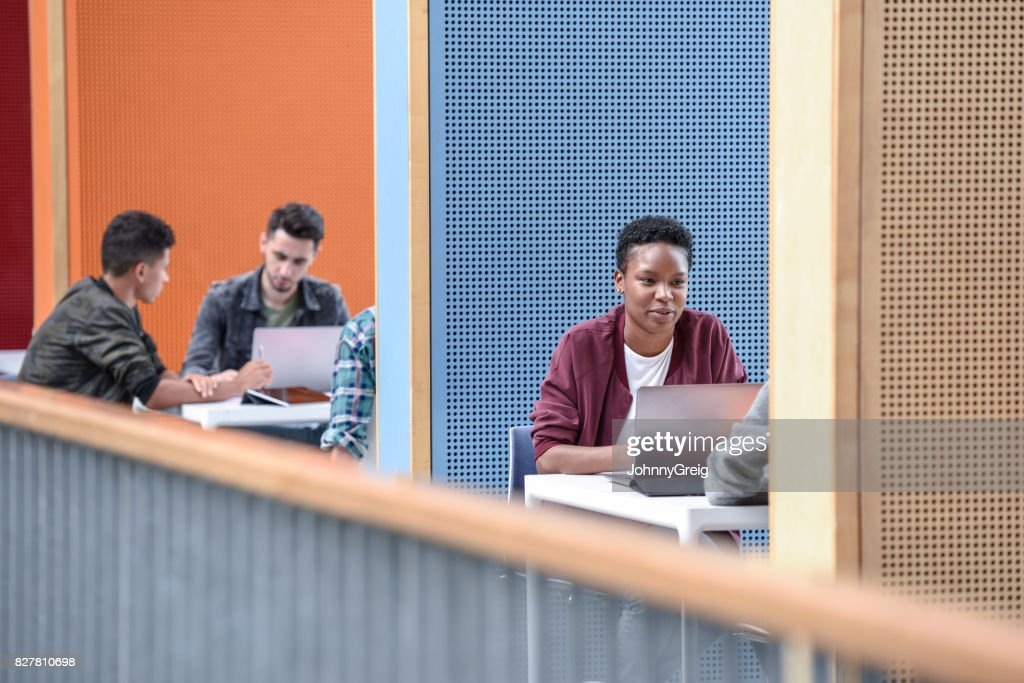 Young female student using laptop in modern booth at college : Stock Photo