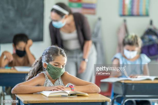young female student wearing a protective face mask in the classroom - fatcamera stock pictures, royalty-free photos & images