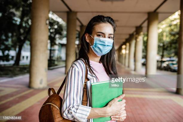 young female student wearing protective face mask during pandemic - college students stock pictures, royalty-free photos & images