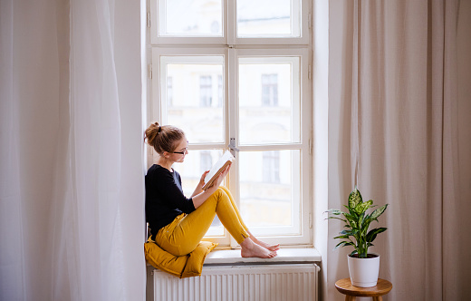 A young female student with a book sitting on window sill, studying. 1156480722