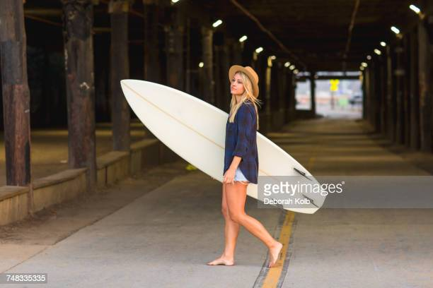 young female surfer carrying surfboard in underpass, santa monica, california, usa - デニムシャツ ストックフォトと画像