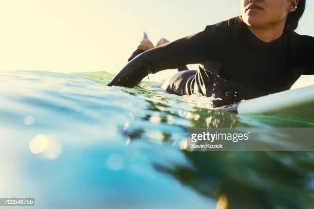 Young female surfer paddling surfboard at sea, Newport Beach, California, USA