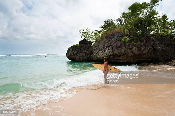 若い女性のサーファーに準備サーフィン