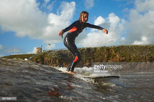 Young female surfer riding wave