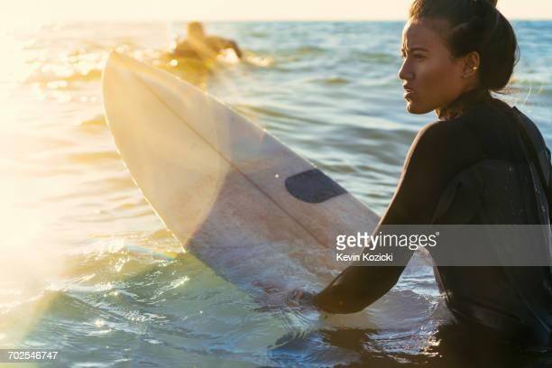 Young female surfer wading in sea, Newport Beach, California, USA