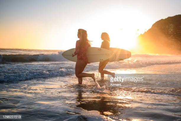 young female surfers running into water at burleigh heads - coral sea stock pictures, royalty-free photos & images