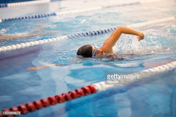 水泳フリースタイルを競う若い女性水泳選手 - 水泳自由形 ストックフォトと画像