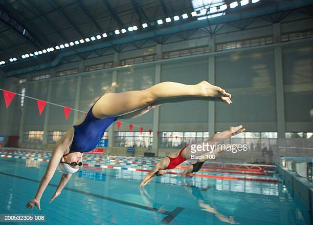 young female swimmers diving into swimming pool, side view - diving sport stock pictures, royalty-free photos & images