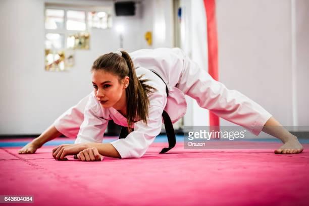 taekwondo femenino joven entusiasta en entrenamiento, calentamiento y estiramientos - taekwondo fotografías e imágenes de stock