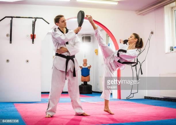Young female taekwondo enthusiast on training, warming up